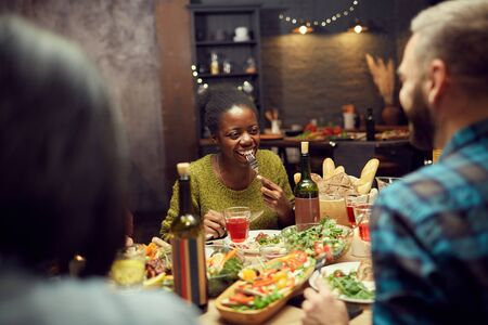 Portrait of young African-American woman smiling happily while enjoying dinner with friends sitting at table in dimly lit room