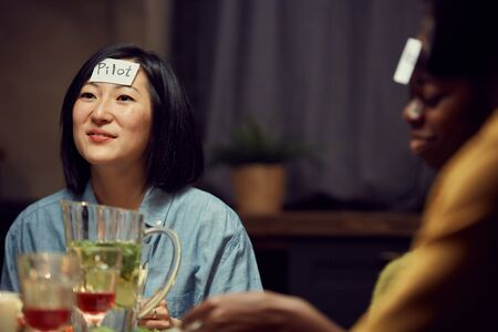 Portrait of smiling Asian woman playing guessing game with friends during party, pilot sticker on her forehead