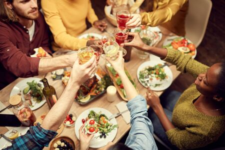 Above view of people raising glasses over dinner table while enjoying party with friends, copy space Imagens