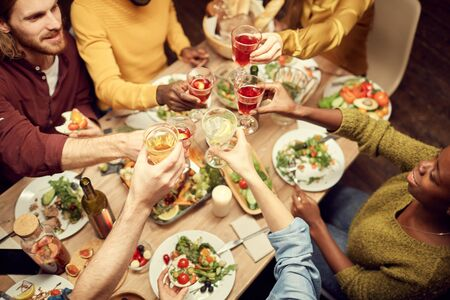 Top view of people raising glasses over dinner table while enjoying party with friends, copy space