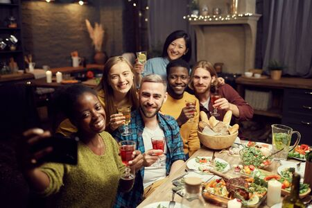 Multi-ethnic group of young people taking selfie photo via smartphone while enjoying dinner party at home, copy space Imagens