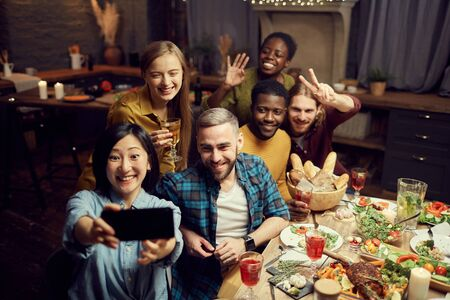 Multi-ethnic group of young friends taking selfie photo via smartphone and smiling happily while enjoying dinner party at home, copy space Imagens