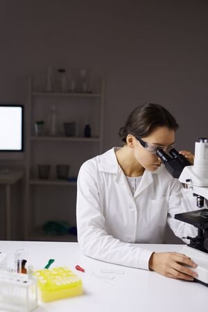 Portrait of young female scientist looking in microscope while doing research in medical laboratory, copy space