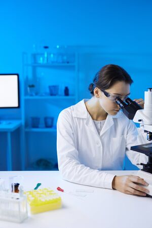 Portrait of young female scientist looking in microscope while doing research in medical laboratory lit by blue light, copy space Фото со стока
