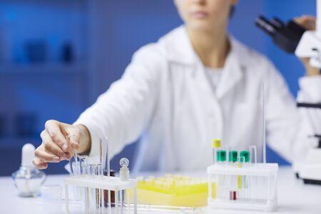 Close up of unrecognizable female scientist holding test tubes while doing research in medical laboratory, copy space