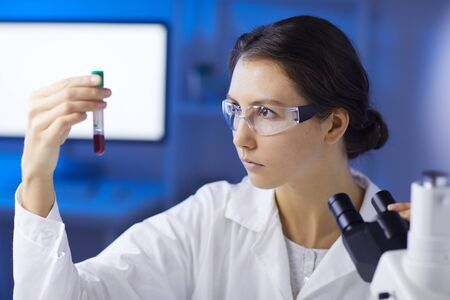 Portrait of young woman holding blood sample while doing medical research in laboratory, copy space