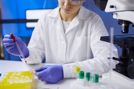 Close up of unrecognizable young woman preparing blood samples while working on research in medical laboratory, copy space