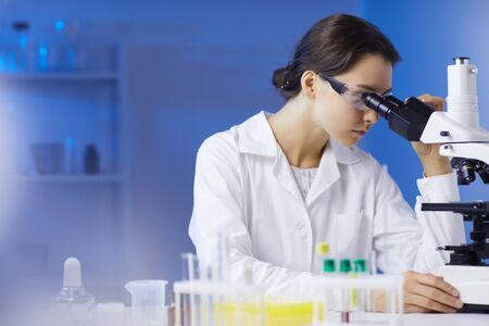 Side view portrait of young female scientist looking in microscope while doing research in medical laboratory lit by blue light, copy space Фото со стока