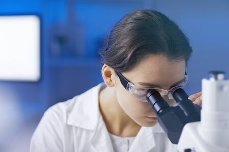 Closeup portrait of young female scientist looking in microscope while doing research in medical laboratory lit by blue light, copy space Фото со стока