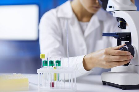 Close up of unrecognizable female scientist setting up microscope while doing medical research in laboratory, copy space Reklamní fotografie