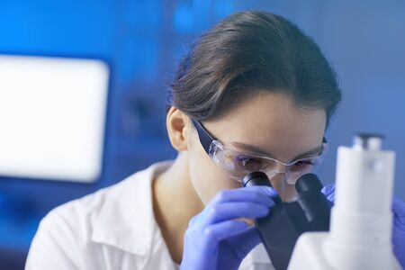 Close up portrait of young woman wearing protective glasses looking in microscope while working on medical research in laboratory, copy space