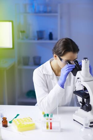 Portrait of young female scientist looking in microscope while working on medical research in laboratory, copy space