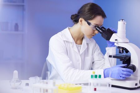 Side view portrait of beautiful young woman looking in microscope while working on medical research in laboratory, copy space