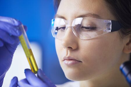 Closeup of beautiful young woman looking at test tube with colored liquid while working on medical research in laboratory, copy space