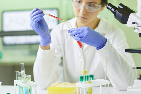 Cropped portrait of young female scientist preparing blood test sample using dropper while working in medical laboratory, copy space Reklamní fotografie