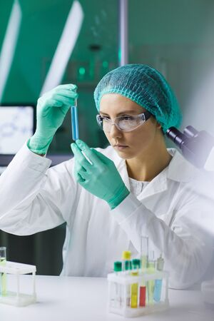 Portrait of young woman holding test tube while working on scientific research in medical laboratory Imagens