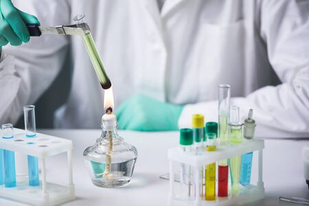 Close up of unrecognizable scientist holding test tube over gas burner while working on research experiment in laboratory, copy space