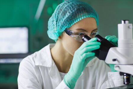 Portrait of young woman wearing protective workwear looking in microscope while working on research in medical laboratory, copy space