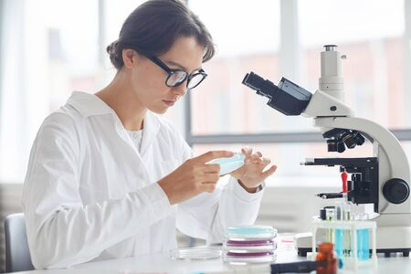 Side view portrait of beautiful young woman working in laboratory holding petri dish for microscope research
