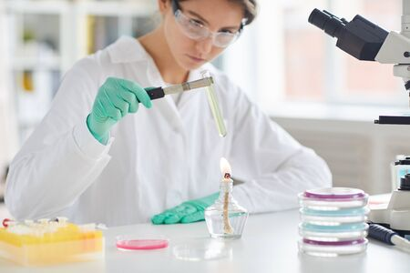 Portrait of young female scientist holding test tube over gas burner while working on research in laboratory, copy space