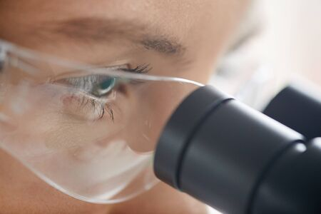 Extreme closeup of young woman looking in microscope while working on research in medical laboratory, copy space