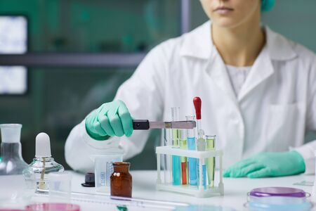 Closeup of unrecognizable woman taking test tube with colored liquid while working on research in medical laboratory, copy space