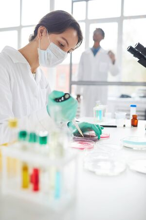 Side view portrait of young woman working in medical laboratory preparing test samples for research, copy space