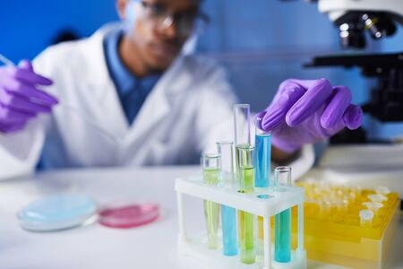 Close up of young African-American man holding test tube samples while working on medical research in laboratory, copy space