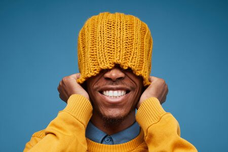 Portrait of emotional African man smiling brightly at camera while pulling yellow knit hat posing against blue background, copy space