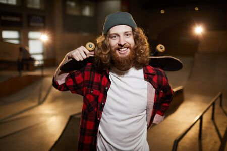 Waist up portrait of cheerful bearded skater looking at camera while posing in urban skating park, copy space Imagens