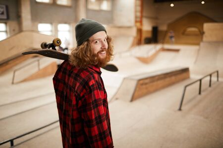 Waist up portrait of hipster man looking at camera over shoulder while posing in skating park, copy space Imagens