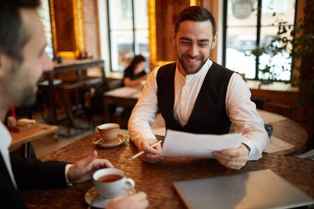 Portrait of successful bearded businessman reading contract and smiling happily while talking to partner during business meeting in cafe