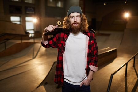 Waist up portrait of contemporary bearded man looking at camera while posing with skateboard in skating park, copy space Imagens