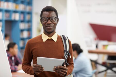 Waist up portrait of smiling African-American student looking at camera while standing in library of modern college, copy space