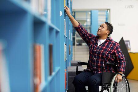 Ritratto di studente disabile in sedia a rotelle che sceglie libri mentre studia nella biblioteca del college, copia spazio