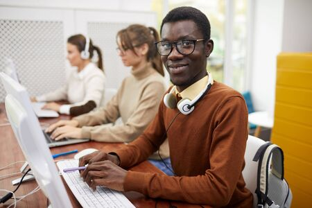 Portrait of young African-American man smiling at camera while using computer in college library, copy space