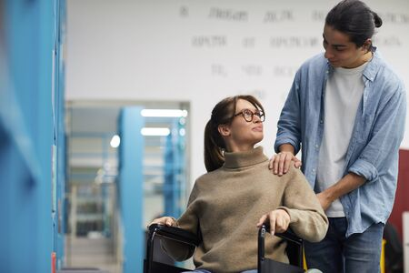 Portrait of young couple, woman in wheelchair, looking at each other and smiling while standing by shelves in library