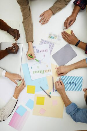 Above view of unrecognizable young people discussing group project and pointing at colorful graphs while brainstorming ideas, copy space Imagens