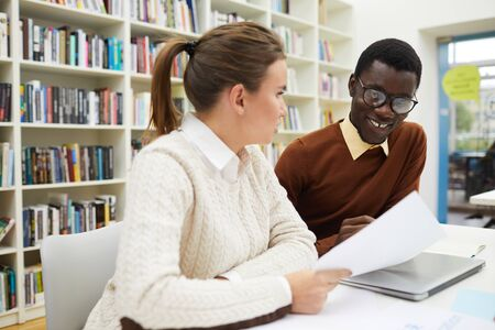 Portrait of smiling African-American student discussing school project with friend while sitting at desk in library, copy space 免版税图像