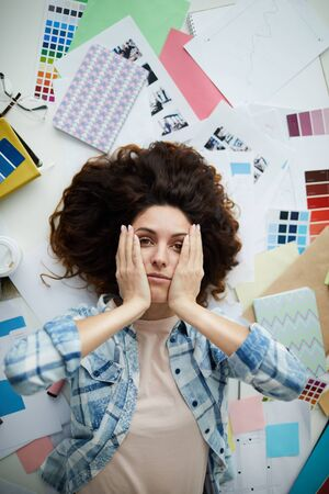 Above view portrait of stressed young woman looking at camera while lying on floor surrounded by art supplies and designer work, copy space
