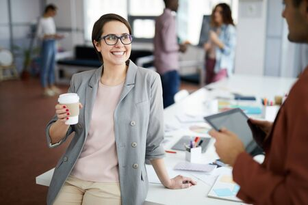 Portrait of modern young businesswoman smiling cheerfully while talking to colleague during coffee break in office, copy space