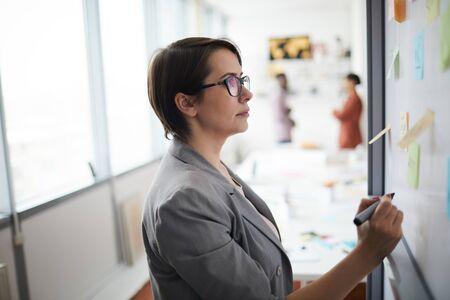 Retrato de vista lateral de la empresaria moderna escribiendo en la pizarra en la oficina, espacio de copia