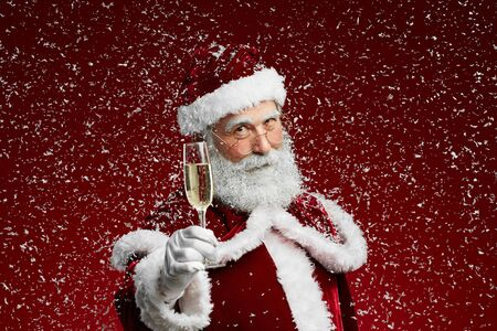 Waist up portrait of Santa Claus holding champagne glass while standing over red background with snow falling, copy space