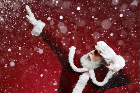 Waist up portrait of funky Santa dancing over red background with snow falling, copy space