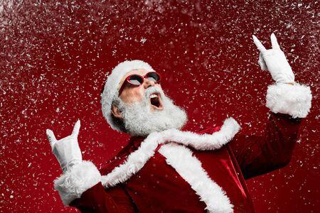 Taillenporträt des coolen Rock-Weihnachtsmannes, der über rotem Hintergrund mit fallendem Schnee brüllt, Kopienraum