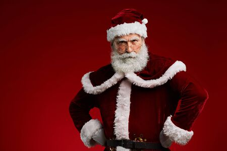 Waist up portrait of frowning Santa Claus standing with hands on hips while posing against red background in studio, copy space