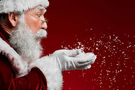 Side view portrait of classic Santa Claus blowing snow while standing against red background, copy space Stock fotó