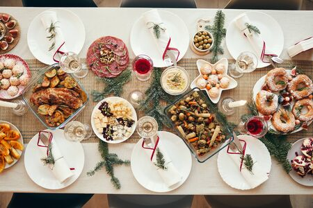 Top view background of beautiful Christmas table with delicious homemade food decorated with fir branches, copy space Stock Photo