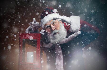 Waist up portrait of fairytale Santa holding lantern walking through snow storm in the night, copy space Banco de Imagens - 133184624