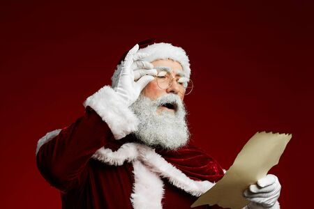 Waist up portrait of classic Santa reading list on parchment standing against red background, copy space Stock Photo